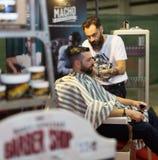 Yrkesmässig frisör som tillbaka rakar av clienhuvudet Arkivbilder