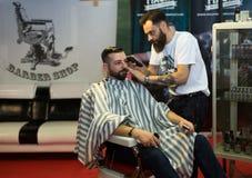 Yrkesmässig frisör som tillbaka rakar av de head männen Fotografering för Bildbyråer