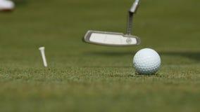 Yrkesmässig golfare som sätter bollen in i hålet Golfboll vid kanten av hålet med spelaren i bakgrund på en solig dag arkivbilder