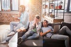 Yrkesmässig grupp som tillsammans sitter på soffan med bärbara datorn och diskuterar royaltyfri bild