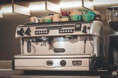 Yrkesmässig kaffemaskin på en grå bakgrund med kulöra cirklar överst av kaffe-maskinen arkivbild