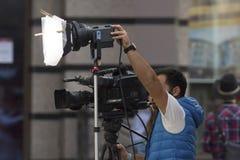 Yrkesmässig kameraman som skjuter en video på gatan Fotografering för Bildbyråer