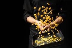 Yrkesmässig kock Kocken förbereder en maträtt med havre i en panna På en svart bakgrund meny receptbok, sund mat, restaurang arkivbild