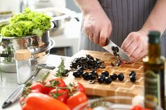 Yrkesmässig kock Slicing Olive Salad Ingredient arkivbilder