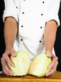 Yrkesmässig kock som visar ett kålsnitt in i två stycken Royaltyfri Fotografi