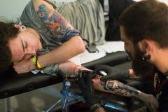 Yrkesmässig konstnär som gör den färgrika tatueringen på klientarmen Arkivfoton