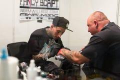 Yrkesmässig konstnär som gör tatueringen på klientarmen Arkivbilder