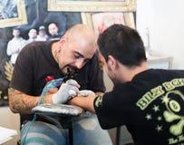 Yrkesmässig konstnär som gör tatueringen på klienthanden Arkivbilder