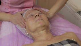 Yrkesmässig kosmetolog som masserar den mänskliga framsidan stock video