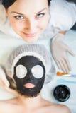 Yrkesmässig kvinna, cosmetologist i brunnsortsalongen som applicerar gyttjaframsidamaskeringen Fotografering för Bildbyråer