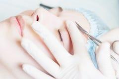 Yrkesmässig kvinna på brunnsortskönhetsalongen som gör korrigeringsögonbrynet Arkivfoto