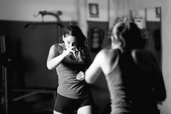 Yrkesmässig kvinnlig boxare som utarbetar, medan se i spegel royaltyfri foto