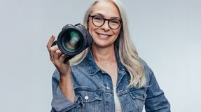 Yrkesmässig kvinnlig fotograf med dslrkameran arkivbild