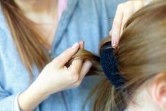 Yrkesmässig kvinnlig frisördanandefrisyr till den gladlynta unga kvinnan med långt hår Arkivbilder