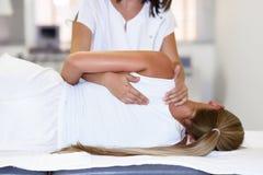Yrkesmässig kvinnlig fysioterapeut som ger skuldramassage till b arkivfoton