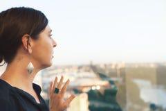Yrkesmässig kvinnlig som ut ser kontorsbyggnadfönstret royaltyfria bilder