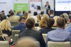 Yrkesmässig kvinnlig värd som framme talar av åhörarna under affärskonferens arkivbild