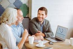 Yrkesmässig le försäkringchef som talar med åldriga par Arkivfoton