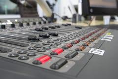 Yrkesmässig ljudsignal operatör som arbetar på ljudsignala blandareknoppar under levande TVTV-utsändning Arkivbilder
