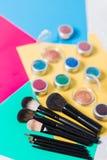 Yrkesmässig makeupborste och skönhetsmedel på en mångfärgad bakgrund royaltyfri foto