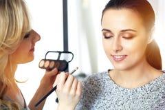Yrkesmässig makeupkonstnär som arbetar med den härliga unga kvinnan Brud-, mode eller näck stil Fotografering för Bildbyråer