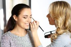 Yrkesmässig makeupkonstnär som arbetar med den härliga unga kvinnan Brud-, mode eller näck stil Royaltyfri Foto