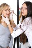 Yrkesmässig makeupkonstnär som arbetar med den härliga unga kvinnan Brud-, mode eller näck stil Royaltyfria Foton