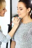 Yrkesmässig makeupkonstnär som arbetar med den härliga unga kvinnan Brud-, mode eller näck stil Royaltyfri Bild