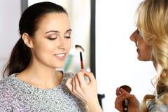 Yrkesmässig makeupkonstnär som arbetar med den härliga unga kvinnan Brud-, mode eller näck stil Royaltyfri Fotografi