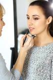 Yrkesmässig makeupkonstnär som arbetar med den härliga unga kvinnan Brud-, mode eller näck stil Arkivbilder