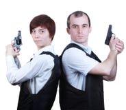 Yrkesmässig man och kvinna med vapen Arkivbilder