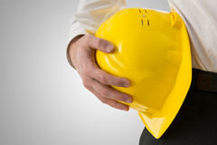 Yrkesmässig man som bär en gul hardhat arkivbilder