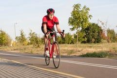 Yrkesmässig manlig cyklist i den Racing dräkten under en ritt Arkivfoton