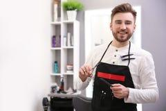 Yrkesmässig manlig frisör med hårkammen och sax Fotografering för Bildbyråer
