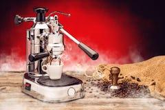 Yrkesmässig manuell silverkaffemaskin med kopp kaffe-, stamper- och säckkaffebönor på röd bakgrund, produktprotography royaltyfri foto