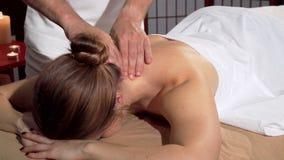 Yrkesmässig massör som gör koppla av tillbaka massagen för kvinnlig klient stock video