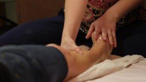 Yrkesmässig massör som gör thai fotmassage Kvinnlig klient som kopplar av i brunnsortsalong arkivfilmer