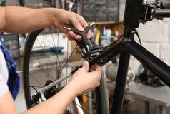 Yrkesmässig mekaniker som reparerar cykeln fotografering för bildbyråer