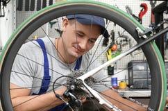 Yrkesmässig mekaniker som reparerar cykeln arkivfoto