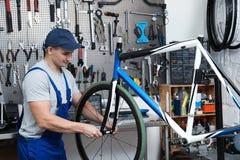 Yrkesmässig mekaniker som reparerar cykeln i modern worksho royaltyfri fotografi