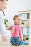 Yrkesmässig pediatrisk undersökande liten flicka arkivbilder