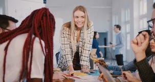 Yrkesmässig positiv kvinnlig ledare som samarbetar med erfarna multietniska kollegor, ledande arbetsplatsdiskussion lager videofilmer