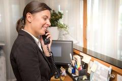 Yrkesmässig receptionist som svarar till en påringning arkivbilder