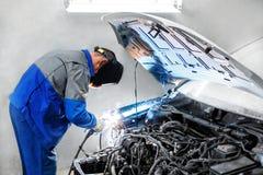 yrkesmässig repairmanarbetare i bil för kropp för bilindustrisvetsningmetall med gnistor Arkivbilder