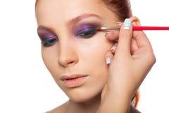 Yrkesmässig sminkkonstnär som gör glamour med röd hårmodellmakeup Isolerad bakgrund Royaltyfri Bild