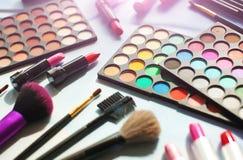 Yrkesmässig sminkuppsättning: ögonskuggapaletten, läppstift, sminkborstar och många skönhetsmedel stänger sig upp Film- och signa Fotografering för Bildbyråer