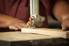 Yrkesmässig snickare som arbetar med sawingmaskinen i seminarium Arkivbild