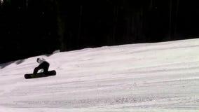 Yrkesmässig snowboarder som glider sluttande utförande bespruta för jippo som är långsamt, i att bedöva extremt landskap för spor arkivfilmer