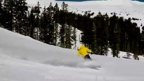 Yrkesmässig snowboarder som glider sluttande utförande bespruta för jippo som är långsamt i ursnyggt extremt landskap för sportku arkivfilmer