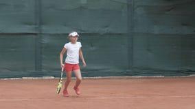 Yrkesmässig sport, tonårs- flicka för tennisspelare som koncentrerar och fokuserar på leken som slår därefter racket på boll på